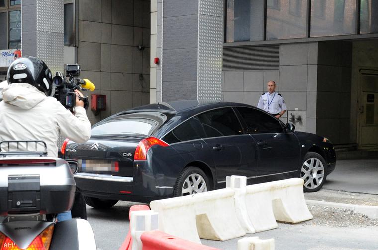 A Sarkozy-t szállító autó érkezik a francia rendőrség anti-korrupciós nyomozócsoportjának irodájába