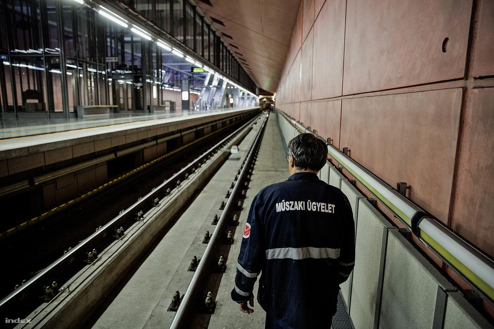 """A baloldalt (és más képeken is látható) sárga-zöld műanyaggal félig fedett oldalsó, """"harmadik sín"""" adja az áramot a vonatoknak. Éjjel, amikor a sínek között dolgoznak, ez áramtalanítva van, de nappal 825 volt egyenáram van benne, ami életveszélyes. A kép jobb oldalán látszik az az érzékelősor, amelyik figyeli, ha valaki beesik a sínek közé. Ilyenkor azonnal kikapcsolja az áramot és megállítja a vonatot is. A sínek között látszik az életmentő árok, ide kell befeküdni akkor, ha már nagyon közel van a metró és látszik, hogy nem fog tudni megállni. Az árok olyan mély, hogy egy ember elfér benne anélkül, hogy a metróhoz érne. A sínek között (a baloldali sín mellett) látszik még a vízköddel oltó csöve is, ebben nagynyomású vizet lehet fújni a pályára, ami úgy tudja eloltani a tüzet, hogy (annak ellenére, hogy vízről van szó!) nem okoz áramütést. Mesélték, hogy az egyik teszt során feszültség alatt volt a pálya, bekapcsolták a vízköddel oltót, bejött a vonat, megállt, majd továbbment anélkül, hogy bármi baja lett volna."""