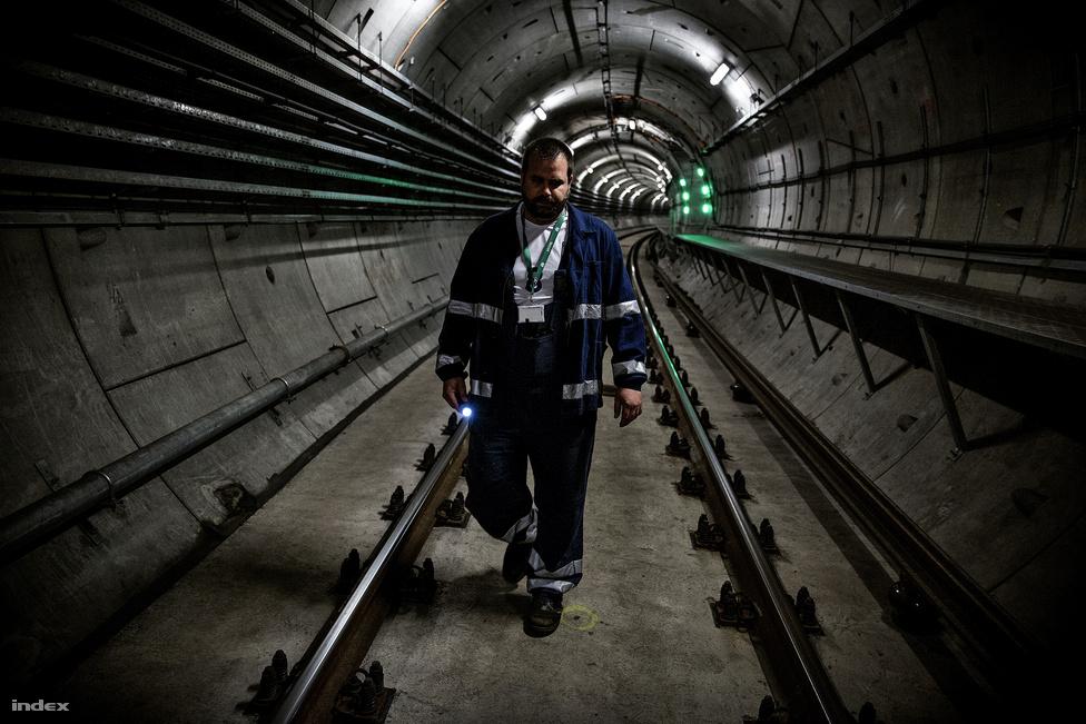 """A síneket és az alagutat minden éjjel átnézik: négy ember indul el a két végállomásról a két alagútban, """"andalgós sétában"""" végigjárják a vonalat, és a sínek rögzítéseit ellenőrzik egy zseblámpával, majd középen találkoznak. Ezek a karbantartók felfelé is néznek, azt ellenőrzik, hogy nem lóg-e be valami a vonat """"aurájába"""". A háttérben zölden világít az egyik menekítőjárat bejárata."""