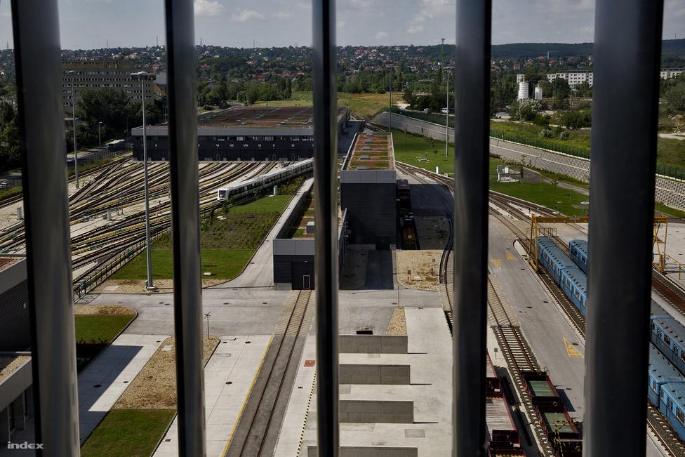 A metró össze van kötve vasúthálózattal is, ez az a sín, amelyik a kép közepén halad a távolba. A metró ugyanolyan nyomtávú, mint a MÁV hálózata, ezért a metrószerelvények is a saját kerekeiken tudnak a vasúti síneken gurulni, de vontatni kell őket. A szerelvények az Alstom lengyelországi gyárából, Katowicéből érkeztek, de nem vasúton, hanem speciális kamionokon. A képen a bal hátsó épület a járműtároló, itt éjszakáznak a metrók, és itt lehet őket lemosni is. A mellette lévő különálló épületben van a kerékpáreszterga, amivel a metró kerekei formázhatók újra, ha a kopás miatt torzulnának. Ez a torzulás egyébként az utasok által is hallható kopogó hangot ad menet közben. Baloldalt a nagy szerelőcsarnok van, ahol fel is lehet emelni a száz tonnánál is nehezebb vonatokat, hogy kereket cseréljenek rajtuk.