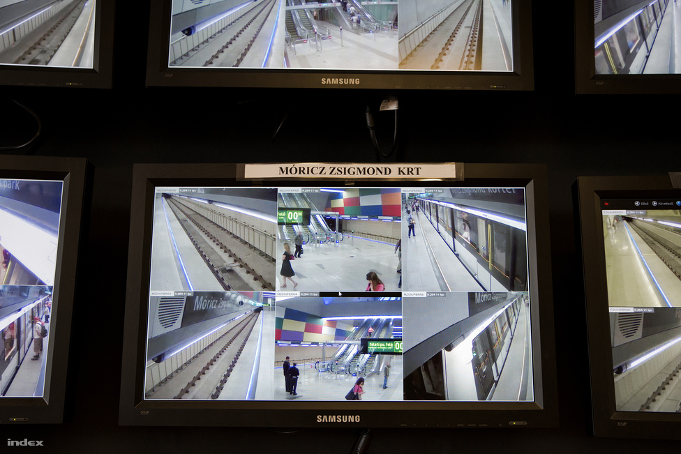 """Az irányítóteremből az összes állomás minden kamerája látható. Amikor ott voltunk, éppen egy kismama szállt be babakocsijával a liftbe. Itt ül az utasforgalmi fődiszpécser, aki innen is tudja irányítani a megállók mozgólépcsőit, a bejárati kapukat, a lifteket. Egy állomás """"átvételére"""" akkor van szükség, ha mondjuk egy baleset miatt az állomáson lévő diszpécsernek el kell mennie a szobájából. Ha valami elromlik az alagútban, vagy valahol elütne valakit a metró, akkor nem kell a teljes vonalat lezárni, mert középen, a Gellért téri állomáson meg tud fordulni a vonat. Így egy ilyen esetben csak az vonal felére kellene pótlóbuszokat szervezni."""