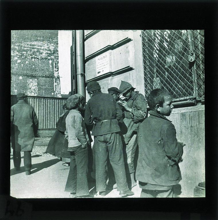 """""""Ezen az 1925-ben keletkezett felvételen ismerős jelenetet látunk: fiúk az utcasarkon. Ám a kis részletek árnyalják a képet: Moszkva egyik szegénynegyedében járunk, az ablakon rácsok, a ruhák koszosak és szakadtak. A cigarettázó fiatalember sapkáját mintha a Vörös Hadseregtől vette volna kölcsön."""""""