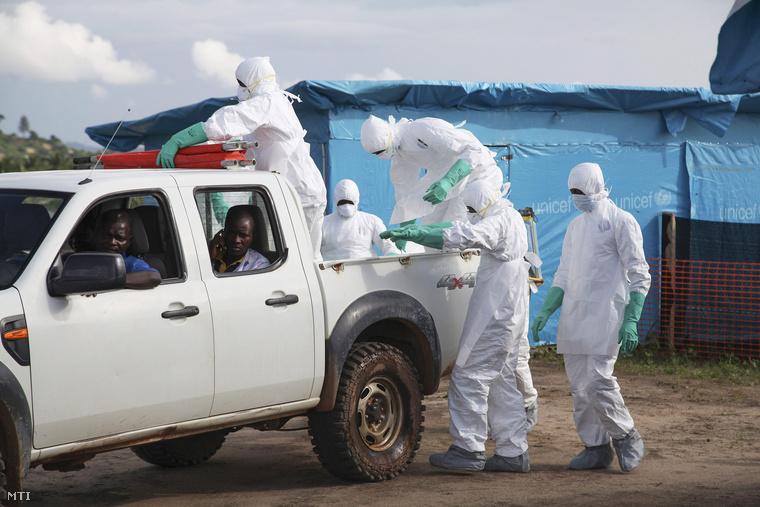 Az ebolavírus egyik áldozatának holttestét viszik temetni védőruhás egészségügyi dolgozók a libériai Foyában 2014. július 2-án.