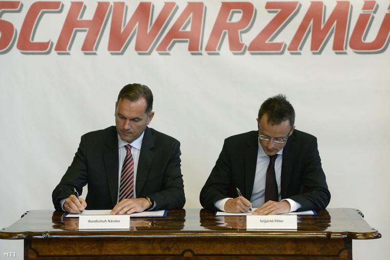 Bundschuh Nándor a Schwarzmüller Járműgyártó és Kereskedelmi Kft. ügyvezető igazgatója (b) és Szijjártó Péter a Külgazdasági és Külügyminisztérium parlamenti államtitkára aláírja a kormány és az autóipari cég közötti stratégiai megállapodást a Parlamentben 2014. július 28-án.