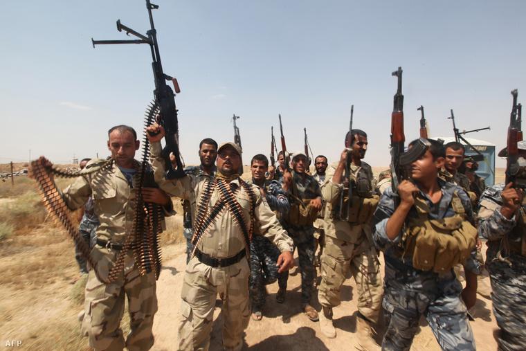 Egy iraki hadsereghez csatlakozott önkéntes csoport fegyveresei pózolnak a kamerának.