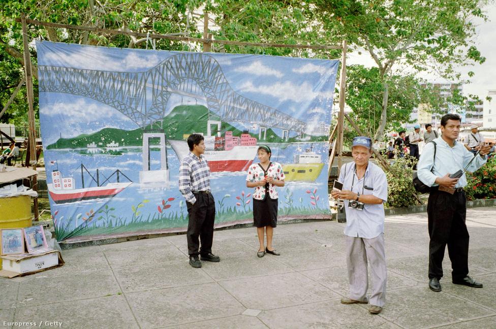Emberek fotózkodnak a Bridge of the Americas hidat ábrázoló paraván előtt 1999. december 28-án, három nappal azelőtt, hogy az USA 85 év után átadja az országnak a csatornaövezet és a csatorna feletti irányítást. Az Egyesült Államok természetesen nem úszta meg ennyivel, az okozott természeti károkért is fizetniük kellett a bérlet lejárta után.