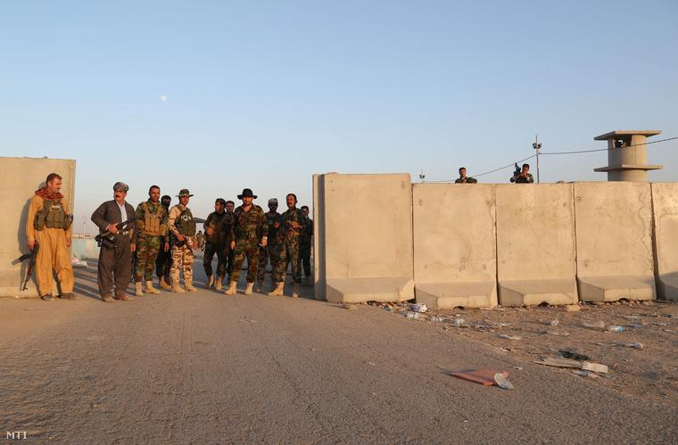 Iraki kurd harcosok azaz pesmergák fedezékbe vonulnak az észak-iraki kurd autonóm területen fekvő Erbíl közelében ahol az amerikai légierő csapást mér az Iszlám Állam (IÁ) szélsőséges iszlamista csoportnak a kurd erőket támadó tüzérségi állásaira 2014. augusztus 8-án.
