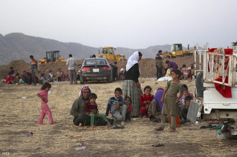 A kurd anyanyelvű iraki jazidi vallási kisebbség tagjai az iraki-szíriai határ közelében fekvő Físhabur városa Badzsjid Kandala menekülttáborának bejáratánál 2014. augusztus 9-én.