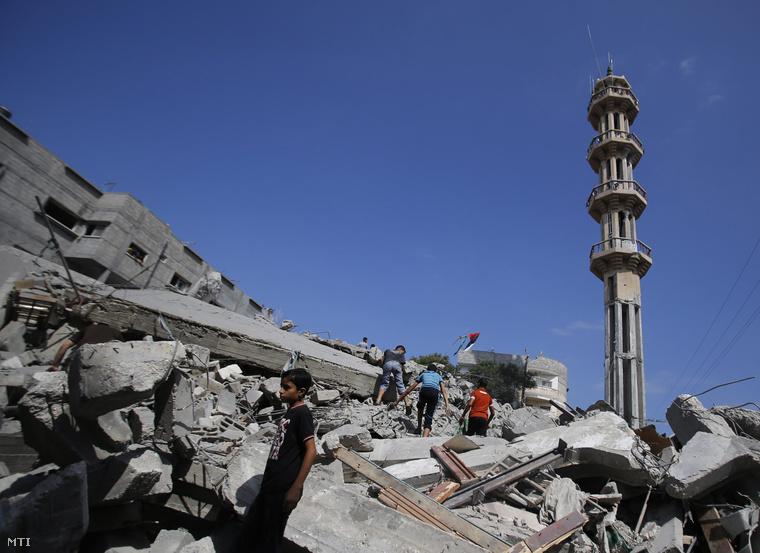Az al-Kaszam-mecset romjainál palesztinok 2014. augusztus 9-én miután izraeli légicsapás érte a templomot.