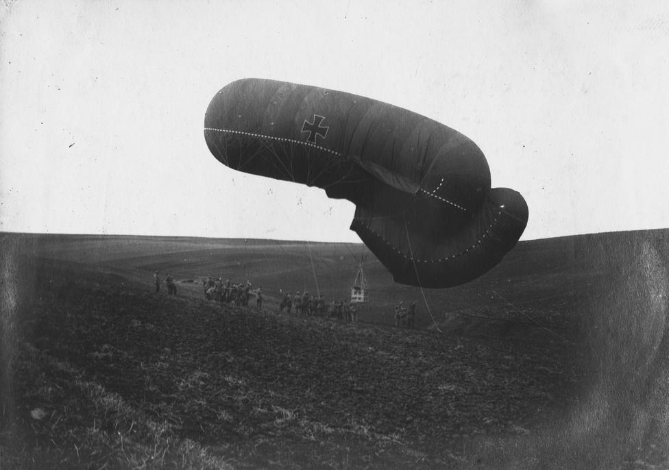 Egy megfigyelésre használt német hőlégballon ereszkedik a mezőre, rajta egy kis kabin – hogy eredetileg is egy kabin csüngött-e rajta, vagy a másikat ellőtték, nem tudni. A német hadsereg sokat adott a légi újításokra, egyfedelűeket és kétfedelűeket röptettek, Zeppelinről is bombáztak, de e fegyvernem inkább ijesztgetésre volt jó, teljes pusztító képességét