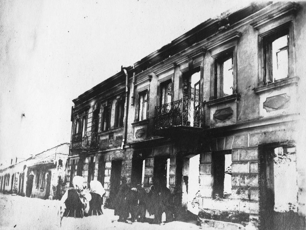 A városka dísze lehetett ez a palota, talán bombát dobtak rá, hogy csak a homlokzata maradt meg. Amikor az orosz visszavonul, mindent feléget, a Monarchiához húzó civilek aztán a bevonuló ezred nyomában jönnek vissza megnézni, mi maradt meg az otthonukból. A két lengyel menyecske távolabbra tart, a kiégett épület előtt talán egy zsidó család álldogál, mintha hirtelen nem lenne ötletük, merre tovább. Az angol sajtóban néha megjelent egy-két cikk 1916-ban, amely felhívta rá a figyelmet, hogy orosz szövetségeseink barbárok, minden ok nélkül gyilkolnak, de a németek belgiumi barbárságairól szívesebben olvasott a nagyközönség. Ami a cs.kir. hadsereget illeti, a kémmizéria rájuk is kiterjedt, sok pópát felhúztak például.