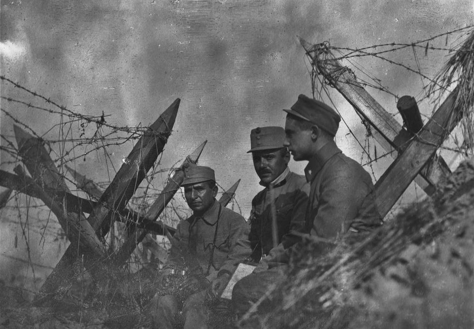 """Három tiszt a két szögesdrótsor között Galíciában, 1914 őszén. Az első vonalba dobták át őket Szerbiából. Az ezred sokat mozog, és minden újabb állomáshelyen le kell rakni a spanyollovasokat, a drótakadályokat. Ha rohamozna az orosz éjjel vagy hajnalban, ezeken fennakad. Nagyobb rohamok után a drótakadályokon halottak csüngnek, akár napokig is, amíg sikerül egy temetési célú tűzszünetben kiegyezni. A férfiak tartalékos hadnagyok, otthon ügyvédek, kereskedők, tisztviselők, gazdálkodók – akinek érettségije van, abból hamar hadnagy lehet. Aki ránk néz középen, vagyis a nagyapám gépébe, hamarosan megsebesül, de már főhadnagyként. Vannak férfibarátságok a fronton, talán ez is egy közülük, három kép van még az albumban erről az ismeretlen férfiről, de a fronton semmi sem tartós, az állandó """"feltöltések"""" és """"átcsoportosítások"""" során – eufemisztikus kifejezések a halottak pótlására és a maradék alakulatok összegyúrására –, nem beszélve a sebesülésről, a halálról és a hadifogságról, megszakad az élő kapcsolat."""