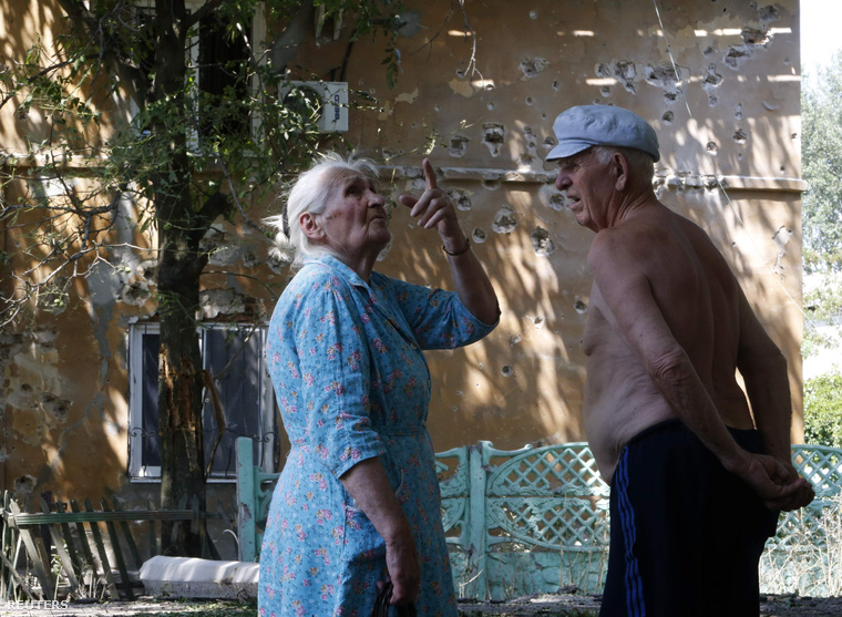 Az ágyúzásban megsérült épület előtt beszélget két donyecki nyugdíjas