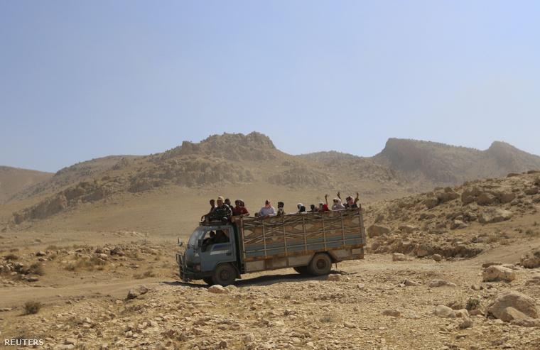 Szindzsárt elhagyó jezidiek egy teherautó platóján
