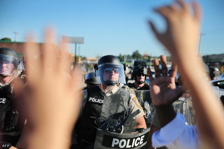 Rendőri sorfal a feltartott kezekkel közeledő tüntetők előtt Fergusonban (augusztus 13.)