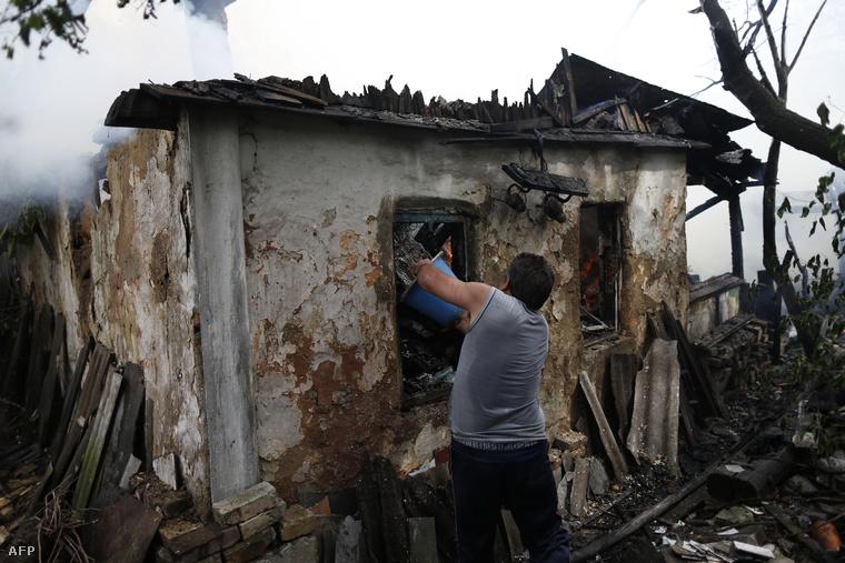 Aknatámadás során kigyulladt családi házát próbálja oldani egy férfi Donyeck külvárosában, 2014. augusztus 17-én.