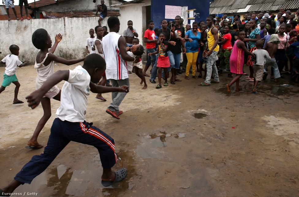 """A karantén egészen váratlan támadásnak is áldozatul esett: tüntető tömeg szállta meg, feltépték a kapukat, a betegeknek megmondták, hogy jöjjenek ki. """"West Pointban nincs ebola!"""" – skandálta a tömeg, a rendőrök figyelmeztető lövéseire sem hallgattak. Végül a megszökött betegekből másfél tucat biztosan visszatért. A képen a tömegből egy férfi kihoz egy beteg lányt a karanténból."""