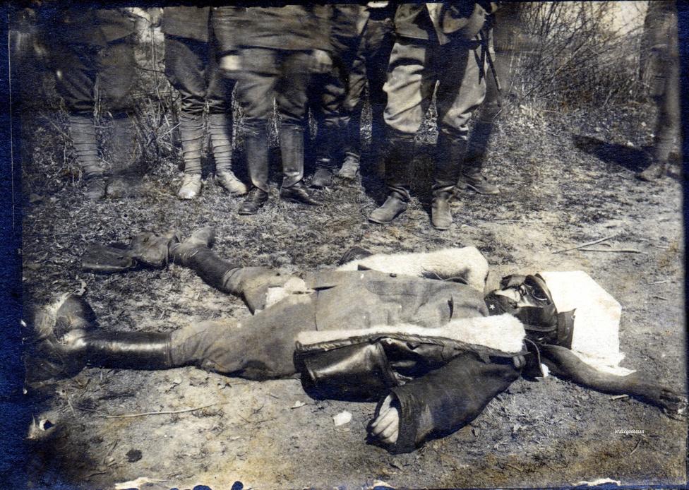 Ismeretlen olasz pilóta holttestét nézik a halált amúgy már rezignáltan fogadó katonák 1917-ben. Bár ekkoriban már rendelkezésre álltak olyan ejtőernyők, amik néha még ki is nyíltak, a pilóták egyszerűen nem használtak ilyesmit. Volt hadsereg, ahol egyenesen megtiltották nekik, nehogy csökkenjen a harci kedvük, de volt olyan pilóta is, aki egyszerűen nem akart felesleges terhet cipelni a gépen. Nem is a lezuhanástól tartottak a legtöbben, hanem a tűzhaláltól: volt, aki azért vitt magával pisztolyt, hogy ha tűz üt ki a gépen, még a borzalmas kínhalál előtt főbe lőhesse magát.