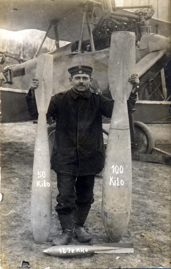 A német légierő földi kiszolgálószemélyzetének egy tagja áll egy kétüléses DFW C.V. típusú, fegyveres felderítőgép előtt. A gép száz kilónyi bombaterhet cipelhetett magával, vagyis a nekünk jobb kézre eső bombából egyet, a balra lévőből kettőt, a katona lábánál heverőből pedig nyolcat vihetett volna (ha lett volna ennyi felfüggesztési pont a gépen). A gépből 3250-et gyártottak, amik nem a háborúban pusztultak el, azokat nagyrészt a békeszerződés értelmében kapták szét. 8 került a német postához, az egyetlen, ma is épségben látható gép pedig Lengyelországban van kiállítva.