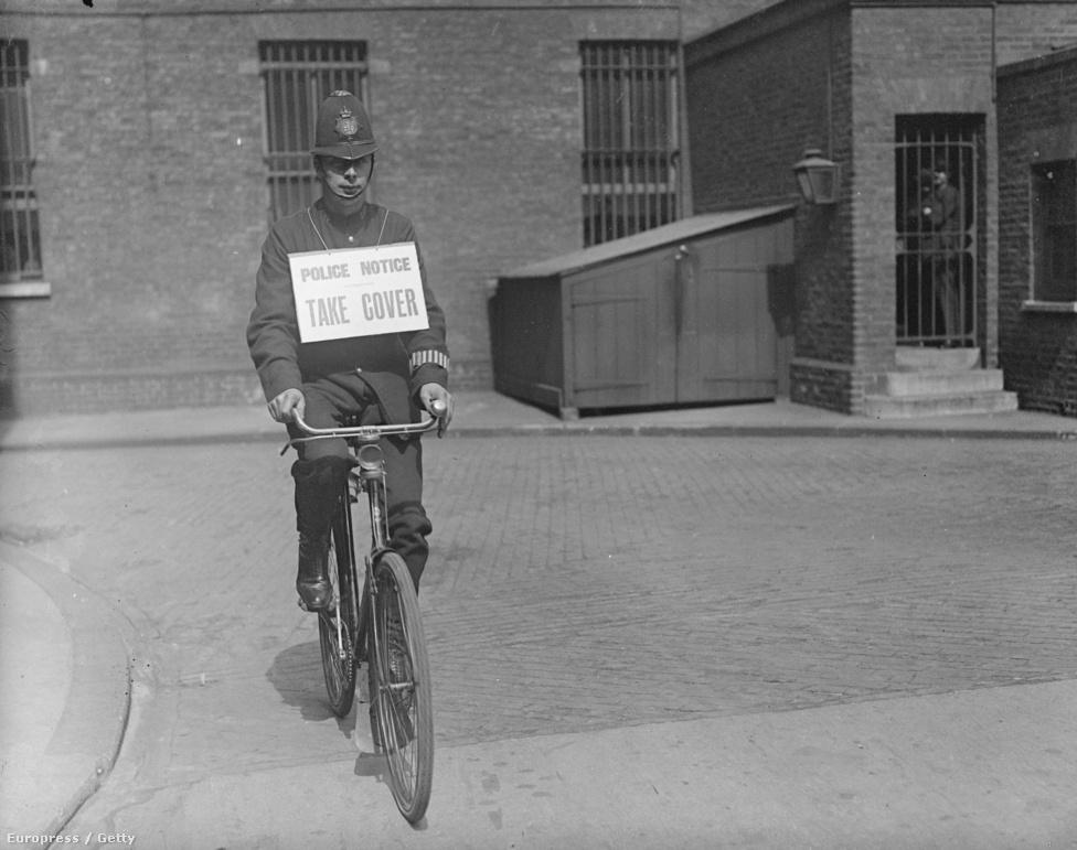 """""""Bújjanak fedezékbe"""", áll a légiriadókor a környéket körbebicikliző rendőr nyakában lógó táblán. 1917. július 14-én készült a kép, ami jól megmutatja, hogy a polgári lakosság védekező mechanizmusa nem fejlődött olyan gyorsan, mint a repülők technikája."""