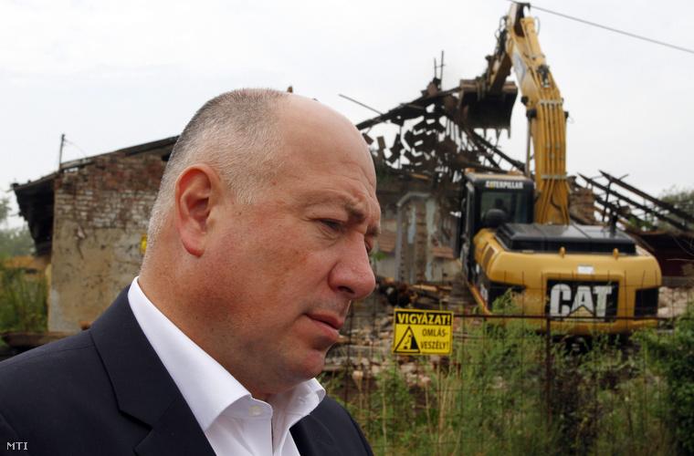 Kriza Ákos polgármester sajtótájékoztatót tart mialatt munkagép bont le egy romos épületet a Dráva utcai nyomortelep felszámolása során a miskolci Martin-kertvárosban 2014. augusztus 8-án.