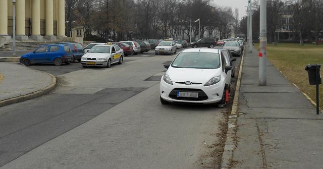 A fehér Ford belóg a templom előtti teresedés után ismét két sávra szűkülő útra. Ezért kapott kerékbilincset