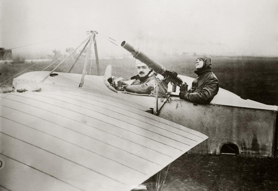Pilóta és lövész egy francia egyfedeles gépben, 1915 decemberében. A háborúban sokáig komoly problémát okozott, hova is tegyék a géppuskákat a repülőkön, ugyanis csak a háború kezdete után, 1915 májusában mutatták be a szinkrongéppuska első változatát. Bár nem Fokker, a híres német mérnök volt az első, aki kitalálta, hogy lehet elintézni, hogy a géppuskák csak akkor tüzeljenek, mikor épp nincs előttük a rotor lapátja, a világháborúban sokáig inkább fémmel vonták be a lapátok tövét, hogy ne nyírják el őket a lőszerek. Később, a két világháború között a nagyobb teherbírású szárnyak megoldották a kérdést: a géppuskákat egyszerűen a rotorlapátok körívén kívülre szerelték fel.