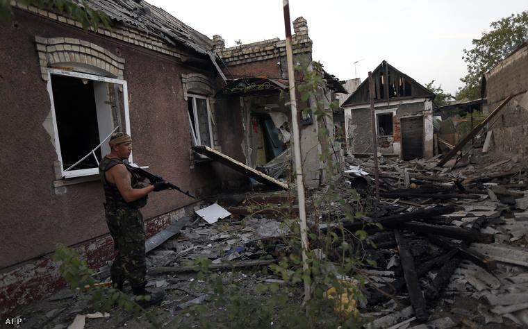 Egy felkelő ellenőrzi a területet Donyeckben az ukrán tüzérségi támadás után.