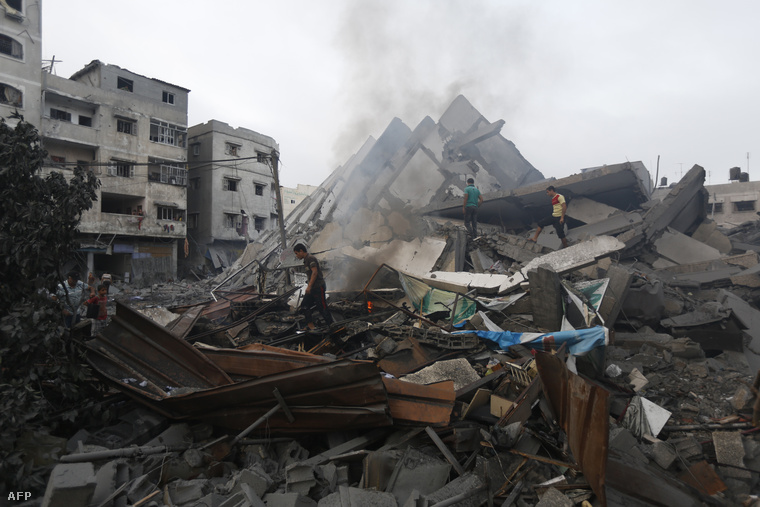 Palesztin lakosok az épület maradványai között Gázában, 2014. augusztus 26-án.