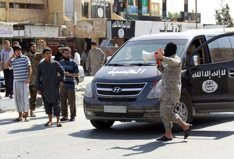 Az ISIS maszkos tagja hangosbeszélőn jelenti be egy Raqqa közeli légibázis elestét egy, a milicisták által elfoglalt településen