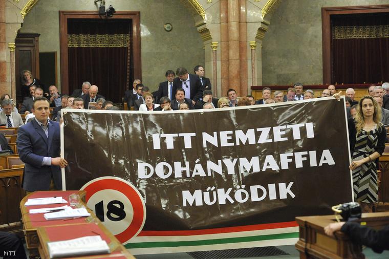 Dorosz Dávid a PM pártigazgatója független országgyűlési képviselő és Szabó Rebeka a PM képviselői csoportjának helyettes vezetője független országgyűlési képviselő egy transzparenst tart a Dohányzással összefüggő egyes törvények módosításáról szóló törvényjavaslat zárószavazásakor az Országgyűlés plenáris ülésén 2013. május 21-én.