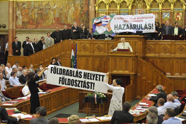 A Jobbik-frakció tagjai tiltakoznak az elnöki emelvényre felvonulva az új földtörvény elfogadása ellen egy A magyar föld átjátszása idegeneknek: hazaárulás! feliratú transzparenssel miközben Szél Bernadett és Osztolykán Ágnes független képviselők az LMP tagjai egy Földrablás helyett földosztás feliratú transzparenst emelnek a magasba a patkóban az Országgyűlés plenáris ülésén 2013. június 21-én.