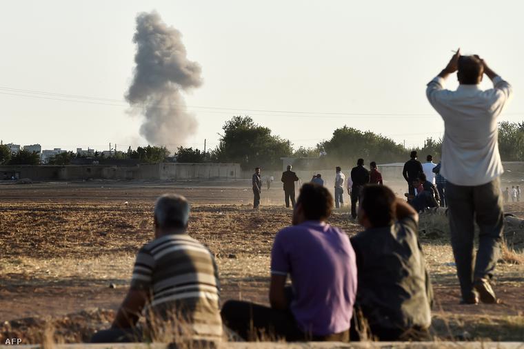 Szíriai kurdok nézik a Kobaniból felszálló füstöt egy szövetséges légcsapást követően, 2014. október 7-én.