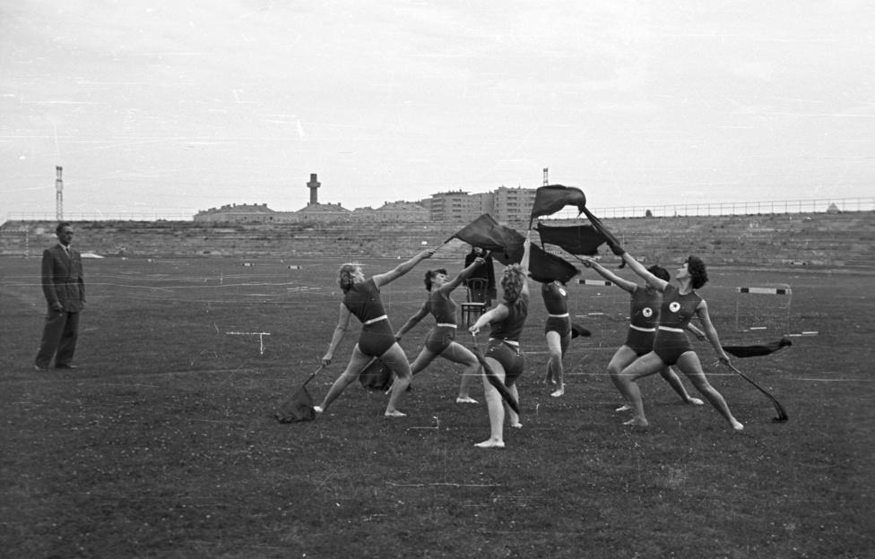 Tornászok gyakorolnak a Fáy utcai sporttelepen, 1955. A sporttelep, ahol a lányok gyakorolnak, csak 1961-től a Vasas labdarúgó-csapatának otthona, akkoriban az Építők pályája volt. A háttérben a Thälmann (ma Fiastyúk) utcai lakótelep házai nőnek ki a földből. Az ötvenes évek egyik presztízsberuházását 1960-ban fejezték be. A kép készítésének idején erőt gyűjtöttek a folytatásra, az első ütem ugyanis 1948 és 1954, a második pedig 1956 és 1960 között valósult meg.