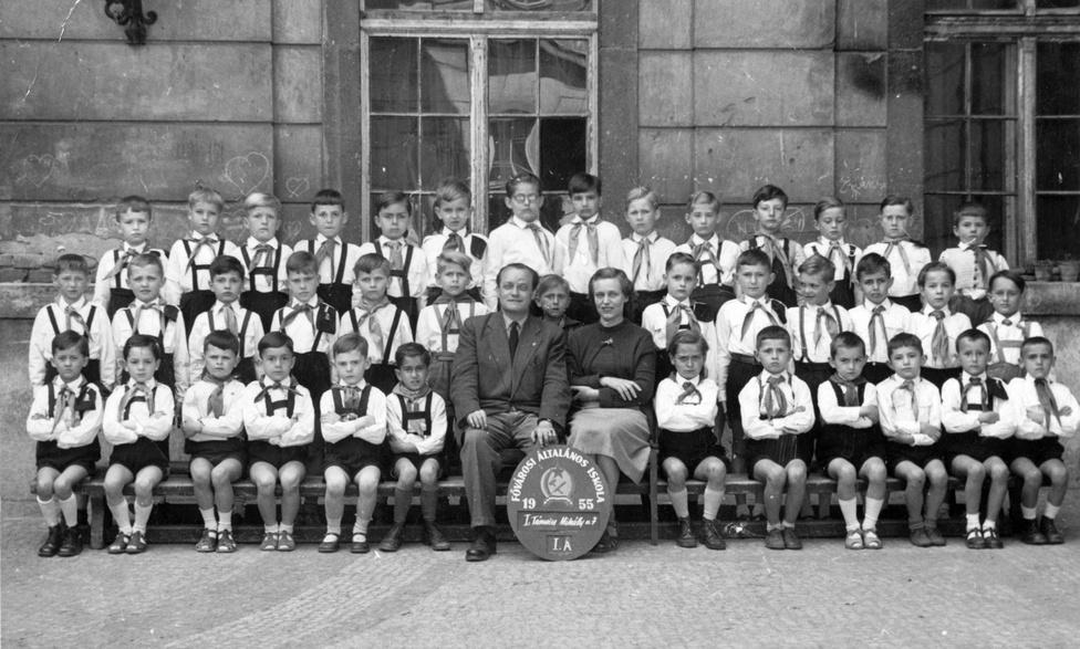 Osztálykép az I. kerületi Táncsics Mihály utcai iskolában, 1955. A magyar iskolákban a rendszerváltásig így néztek ki az osztályképek: vigyázzban ülő és álló gyerekek komolyan néznek bele a kamerába. A 18. század közepén épült volt Erdődy-palotában már régóta nincs iskola, 1984 óta az MTA Zenetudományi Intézete működik a falai között. Magyarország német megszállása alatt itt voltak a Waffen-SS parancsnokságai, valamint ide költözött be Georg Keppler SS-Obergruppenführer. Sőt, hatalomátvétele előtti hetekben maga Szálasi Ferenc is itt lakott, mivel a németek tartottak letartóztatásától.