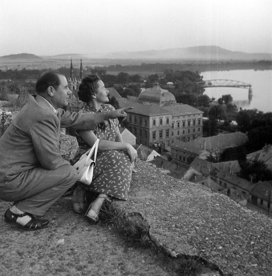 Esztergomi idill, háttérben a felrobbantott Mária Valéria híd, 1955. A zoknira húzott szandált viselő férfi a baráti Csehszlovákia felé mutat kedvesének, csak remélni tudjuk, hogy nem ellenséges szándékkal. Ennél azonban jóval érdekesebb a Mária Valéria híd torzója, ami a második világháború végétől az ezredfordulóig késztette elgondolkodásra Esztergom és a túloldali Párkány lakóit és látogatóit. Az 1895-ben átadott, Ferenc József lányáról (engedéllyel!) elnevezett hidat kétszer rombolták le. Először az első világháború után csehszlovák légionáriusok, majd a második világháború utolsó hónapjaiban visszavonuló német csapatok. Az első világháború után nyolc, a második világháború után ötvenhét év telt el az újabb hídavatásig.