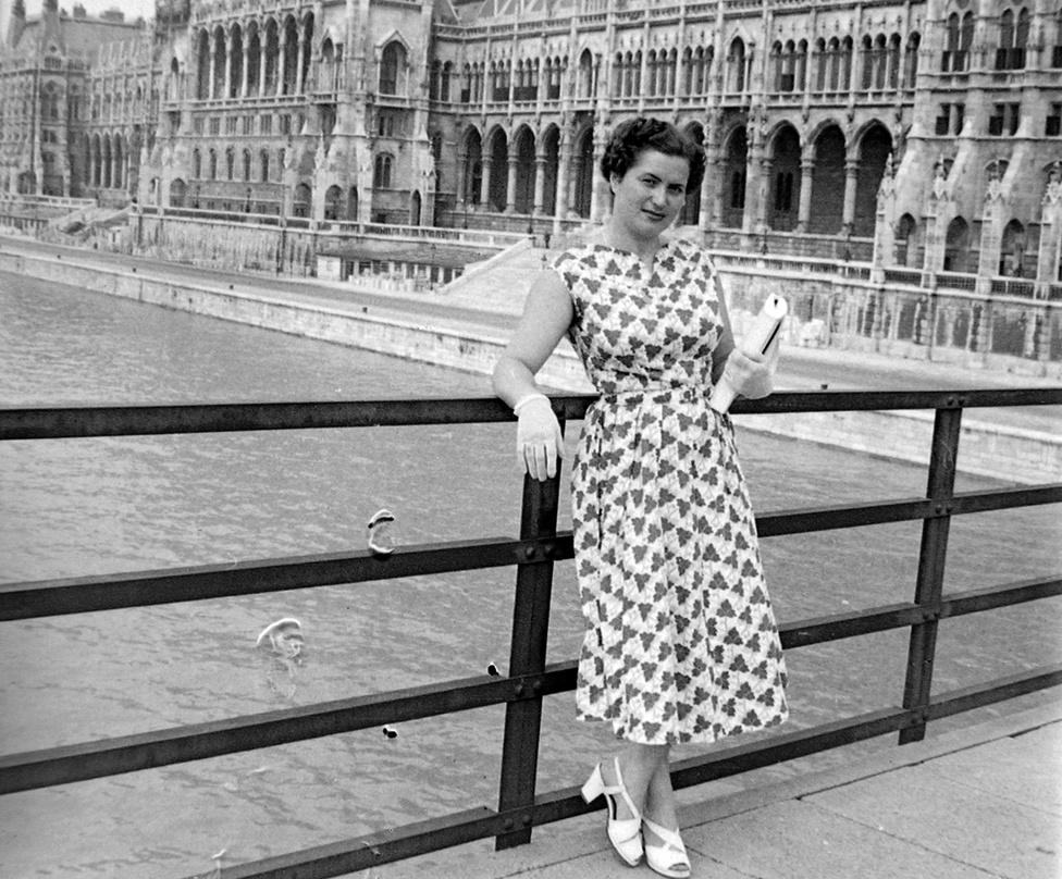 A budapesti Kossuth híd, háttérben a Parlament, 1955. A Kossuth híd a Kossuth teret kötötte össze a Batthyány térrel, miután a második világháborúban megsemmisültek a budapesti Duna-hidak. Ez már nem pontonhíd volt, nem volt kitéve a jégzajlásnak. A hidat mindössze hét hónap alatt építették fel, 1946 januárjában nyitották meg, a vasat a háborús törmelékek adták. A budapestiek Mancinak becézték, és még egy szocreál színdarabot is írtak róla (Háy Gyula: Az élet hídja). A hidat tíz évre tervezték, 1957-ben lezárták, 1960-ban elbontották. A híd keszonjait a Duna-menti Kulcs partvédműveibe építették be. A képen látható hölgy sorsa ismeretlen.