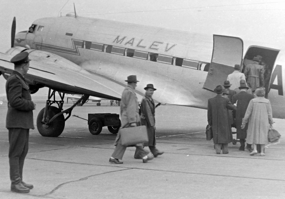 A Malév Liszunov Li-2  típusú gépe a Ferihegyi repülőtéren, 1955. A gépet 1939 és 1952 között gyártották a Moszkva melletti Himkiben, illetve Taskentben, miután a második világháborús német támadás miatt evakuálni kellett a gyárat. A Liszunov Li-2-est a szovjetek az amerikai Douglas DC-3-as gyártójától vett licensz alapján fejlesztették ki. Ezek a gépek (öt darab) voltak a második világháború utáni magyar polgári légiközlekedés első repülőgépei, és nem a Szovjetunióból, hanem Romániából érkeztek. A Malév 1954-ben alakult, miután kivásároltuk a szovjetek részét az addigi közös légitársaságból. A kép készítésének időpontjában a Malév még zömmel belföldre, például Szegedre, Szombathelyre, Győrbe járt, a bécsi járat csak 1956-ban indul meg. A forradalom leverése után egy évig a szovjetek minden repülést betiltottak, az első újraindult járat a Budapest-Miskolc-Debrecen volt.