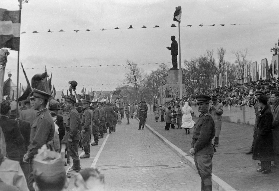 A forradalom előtti utolsó május elsejei felvonulás a Városligetben, 1956. Alig fél évvel később az egykori Felvonulási téren magasodó Sztálin-szobrot ledöntik a forradalmárok. A második világháború óta romos Regnum Marianum templomot és a Városligeti Színház épületét kellett eldózerolni, hogy a nyolc méter magas Sztálin-alakot fel lehessen állítani. Az 1951-es szoboravatáson nyolcvanezer ember vett részt. A szobrász Mikus Sándor 1982-ben halt meg, és nem ez volt az egyetlen szobra, amit ledöntöttek, lebontottak vagy a szoborparkba szállítottak. A budapesti Guszev-kapitány, a vecsési parlamenter-emlékmű vagy a Szabad Nép székház domborműve nincs már a helyén, de a ma is álló zalaegerszegi Nő mandulaággal, a miskolci Fiatalok vagy a jakartai Anyaság láttán senki nem gondolná, hogy alkotója monumentális Sztálint is készített valaha. A szobrot a forradalom első napján döntötték le, miután a Nemzeti Színháznál összegyűlt tömegben felvetődött az ötlet. A hatalmas szoborra hiába kötöttek drótkötelet, négy-öt teherautóval sem lehetett megmozdítani. Végül lángvágóval elvágták térd alatt, így már le lehetett dönteni. A talapzaton sokáig csak a csizmák maradtak. A következő május elsején már Kádár János beszélt egymillió ember előtt a téren. A Kádár-korszakban a szobor talapzatából dísztribün lett, innen integettek az elvtársak a felvonulóknak.