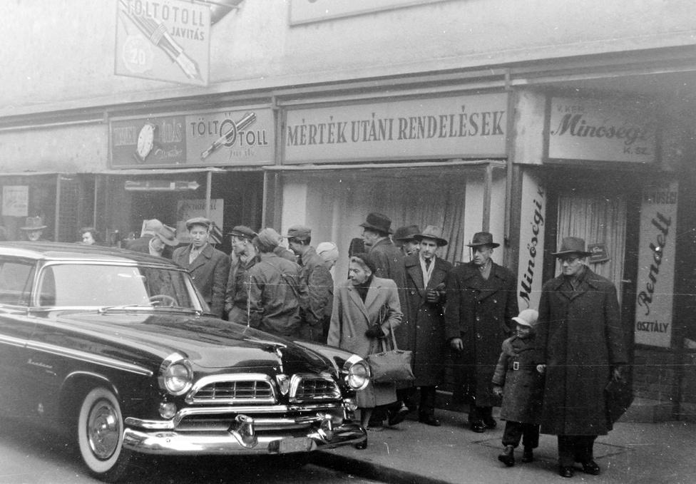 Egy diplomata-rendszámú Chrysler Windsort csodálnak a járókelők a Váci utca 20. előtt. Az autót 1939-től 1961-ig gyártották a michigani  Highland Parkban, 1966-ig már csak Kanadában. A Váci utca 20. számú ház a második világháborúban megrongálódott, csak a földszint maradt meg, ahol kisboltok működtek. Most itt áll a Mercure hotel.