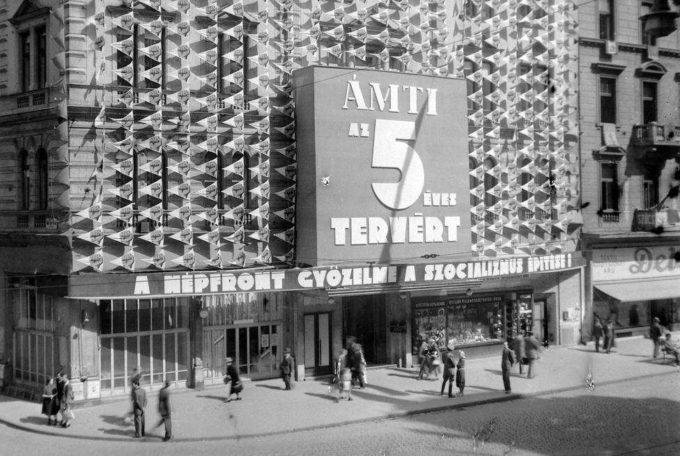 Az Állami Mélyépítés-tudományi Intézet (ÁMTI) székháza Budapesten, a Rákóczi út 58. alatt, 1955. Az épületet szállodának építették, 1896-ban Petanovics József itt nyitotta meg a Metropolt. A második világháború után költözött ide az ÁMTI, majd 1957-től ismét szálloda lett. Az épületen az ötéves tervet reklámozzák a kor divatjának megfelelően. Az első ötéves terv 1954-ben ért véget. Az 1955-ös évet a következő ötéves tervre való felkészülésnek szánták, de végül csak 1958-ban indulhatott meg a második hároméves terv, mindannyian tudjuk, hogy miért. A magyar történelem utolsó ötéves terve éppen az első szabad választások évében, 1990-ben ért véget. És hogy mi volt az ötéves terv? Természetesen szovjet mintára létrehozott, a nemzetgazdaságot szabályozó intézmény, ahol a feladatokat minden termelő egységnek előírták. Jellemző volt, hogy a kitűzött időnél hamarabb teljesítették, de hogy akkor miért omlott össze a szocializmus, az rejtély.