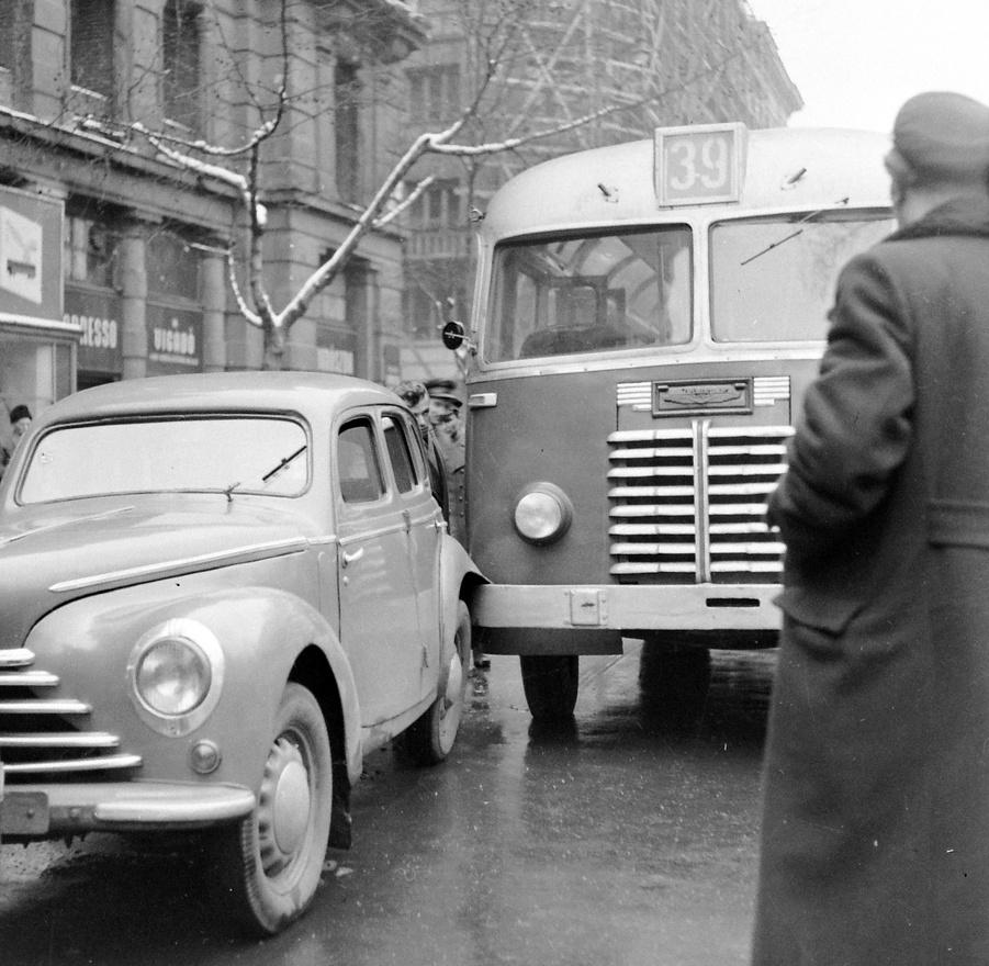 A 39-es busz balesete a Vörösmarty téren, a Haas-palota előtt, 1955. A 39-es busz akkoriban még átment Pestre, a János kórháztól indult, és a Mártírok útja (ma Margit körút), Margit híd útvonalon érte el a Vörösmarty téri végállomását. A vonal leghíresebb balesete 1954-ban történt, amikor egy utasok nélküli 39-es áttörte a Margit híd korlátját és a Dunába zuhant. A sofőr és a kalauz életét vesztette. Az Ikarus 30-as buszokat 1951-től kezdték gyártani, 1956-ig szállították a Fővárosi Autóbuszüzemnek, a csúcson 192 futott belőlük. A Budapesten maradt buszokat 1962-ban selejtezték le, a többi vidéken futott. A Vörösmarty téri impozáns Haas-palota (Haas Fülöp és fia szőnyegcég tulajdona) a második világháborúban bombatalálatot kapott. 1971-ben a helyén épült fel az Országos Rendező Iroda tájidegen kockaépülete. Ezt 2005-ben lebontották, helyén üveg- és acélhomlokzatú irodaház épült.
