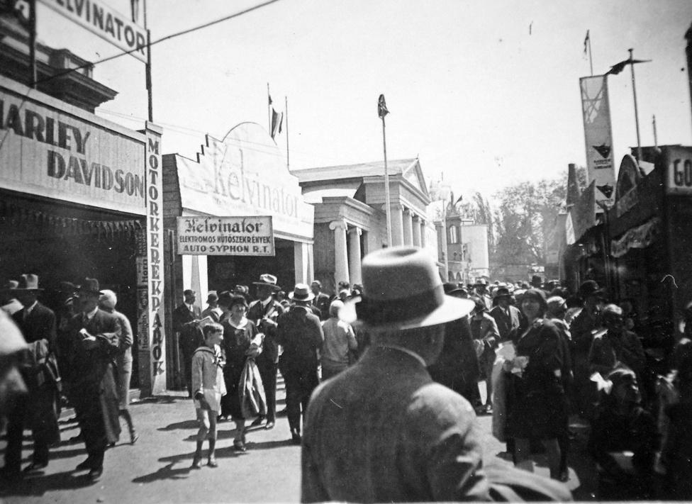 """A Városligetben már az 1880-as években is tartottak vásárokat, de a terebélyesedő, országosból nemzetközivé lett események egyre inkább ütköztek a terület elsődleges pihenőfunkciójával. A Tavaszi Vásárok helyébe 1925-től a minden ében megrendezett Budapesti Nemzetközi Vásárok léptek. A nagy érdeklődés miatt ezek már bőven kinőtték az Iparcsarnokot, még a Műcsarnokot is elfoglalták: itt 1929-ben például rádiókat állítottak ki műalkotások helyett.                         """"Nyilvánvaló, hogy ez a megoldás, amellyel vásárterületté tesszük a Városliget egyes utszakaszait, nem mondható ideálisnak sem a város, sem a vásár szempontjából. Elodázhatatlannak kell ezért most már tartanunk Budapest uj és végleges kiállitási területének létesitését."""" - írták már ekkor; de a BNV csak 1974-ben költözhetett ki Kőbányára."""