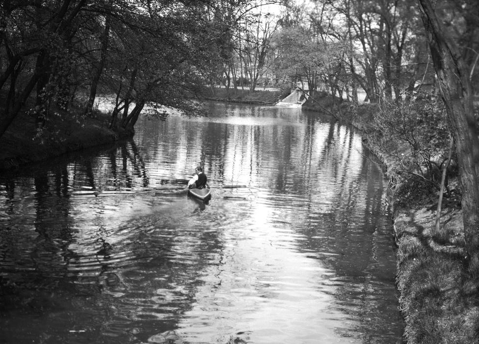Kajakozás ingben-mellényben, 1916-ban. Nem tudjuk, ki ez az úriember, aki a budapesti lakosságra ekkor már teljes erejével lesújtó háborús szegénységről tudomást sem véve csolnakázik a nyugodt víztükrön, feltehetően nem a frontról hazatérő egyszerű baka, pedig egyébként ők lepték el ekkoriban a Városligetet. Ingyenes állatkerti belépővel felvértezve töltötték itt a honvédek megérdemelt kimenőjüket, a sebesült katonák mankókkal is megrohanták a ringlispíleket. A mutatványosbódék jósnői a feltett kérdésekre bizonyára fejből is megfontoltan válaszoltak, a vészjóslóan kavargó jósgömbbe ekkor már nem volt értelme belenézni.