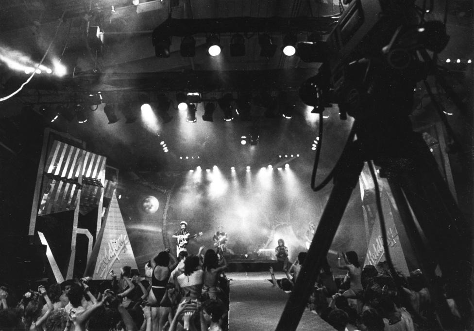 """Szilveszteri TV-felvétel a PeCsában. A Petőfi Csarnok az ország első ifjúsági szabadidőközpontjaként Kathago koncerttel nyitott 1985-ben a volt BNV helyén. Ezen csak pár százan voltak, nem úgy, mint két évvel korábban a városligeti szánkozódombon, az István, a király ősbemutatóján - akkor 120 ezren voltak ott. A PeCsának eleinte egész kedvező építészeti kritikái voltak, de igazán senki nem szerette meg a helyet. A """"Múzeumi Negyed"""" projekt keretében a Petőfi Csarnokot hamarosan lebontják, a kulturális-turisztikai élményparkra irányuló, erősen vitatott gigaberuházás radikálisan átszabja majd a Városligetet."""
