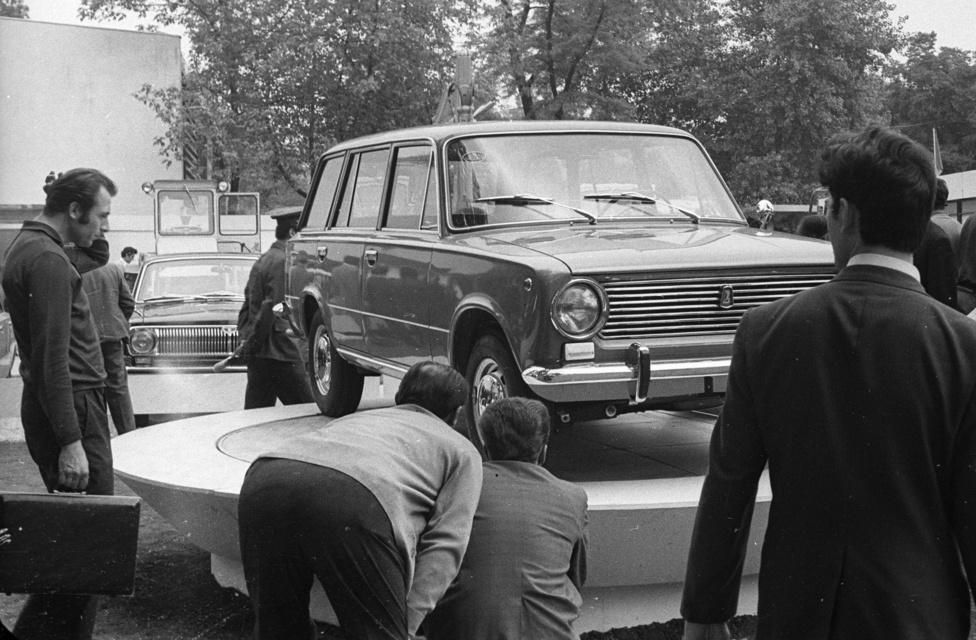 Kombi 1200-es Zsiguli az 1972-es BNV-n. A Fiat 124 alapján gyártott szovjet kocsit ekkor hozták be Magyarországra, az egyszerű vásárlónak persze még éveket kellett várnia, hogy sorra kerüljön a Merkurnál és boldog tulajdonosa lehessen a strapabíró népautónak. A zöldségesek kedvence körül megannyi csodás részlet: a szakértői pillantások, a hajsimítós-aktatáskás tervezgetés mellett a klasszikus stílben kivitelezett, hátratettkézben gumibotos rendőrjárás is figyelemre érdemes.