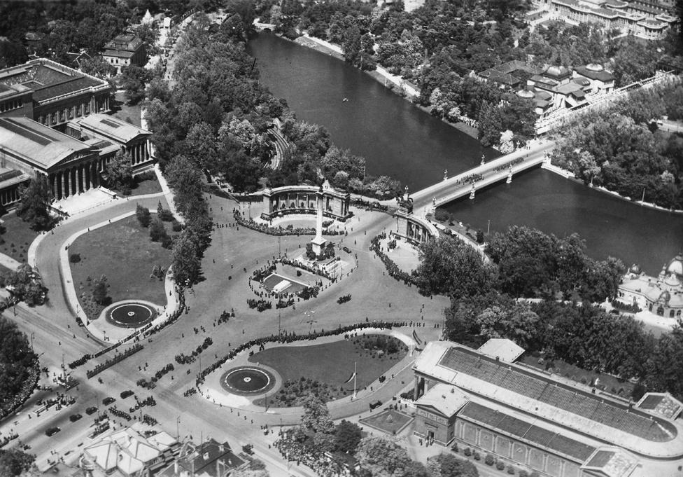 1935-ös legifelvételen a még parkos, virágágyásokkal díszített Hősök tere. A térre bekanyarodik az Állatkerti körút fasora is. Nem látszik jól, de az Andrássy út végén a buszmegálló kialakítása azért mutatja, hogy ekkor még baloldali közlekedés volt Magyarországon, a Jobbra tarts!-ot csak 1941-ben hirdették ki.
