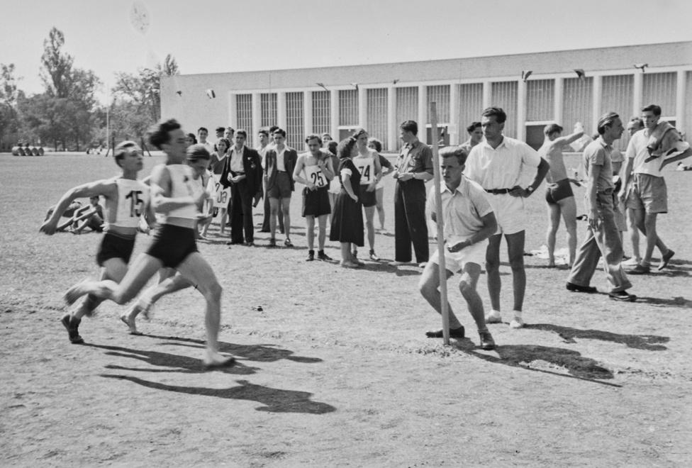 Városligeti sportnap, férfi futóverseny. Háttérben az egykori Iparcsarnok helyén kialakított pavilon. A kommunista hatalomátvétel után a Valjdahunyad várából szovjet mintára Uttörőpalotát akartak csinálni, hogy a kispajtások nevelése az iskolai tanórákon kívül is szocialista szellemben folytatódhasson. A gótikus ívek alatt többek között fémmegmunkáló műhelyt hoztak volna létre, de a tervekből végül nem lett semmi, idővel a Mezőgazdasági Múzeum is visszaköltözhetett az épületbe.