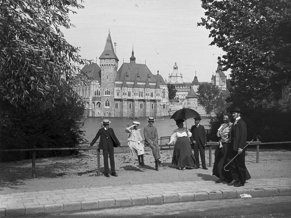A tó, háttérben a Vajdahunyad vára, 1907. Bár az akkor még két nagy szigetet is körbeölelő Városligeti tavat már az addig mocsaras terület első rendezésénél, az 1700-as évek közepén kialakították, mai formáját csak az 1896-os milleniumi kiállításra kapta meg.                         Az Ezredéves Országos Kiállítás a magyar államiság és nemzeti teljesítmény valaha volt legnagyobb reprezentatív csinnadrattája lett. Mikor a Népligettel és Lágymányossal szemben úgy döntöttek, hogy a Városliget legyen a helyszín, még csak ideiglenes építményekben gondolkodtak. A legtöbb kiállítási pavilont és a török kort idéző  mulatóközpontot, a megkapó történelmi giccsként pompázó Ős-Budavárát később valóban lebontották, de a történelmi kiállításoknak helyt adó Vajdahunyad vára megmaradt. A kiállításra gyorsan, fából emelt eklektikus együttest népszerűsége miatt egy évtized múlva tartós anyagokból építették újra.