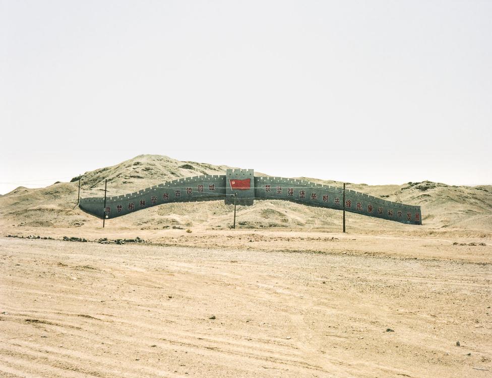 Propagandaüzenettel megbolondított disneyland-ihletésű álfalrészlet a Góbi-sivatagban. Történelmi kínai fal-erődítmények egyébként léteztek a mai Észak-Korea, Mongólia és Oroszország területén is.